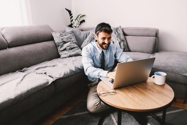 Programista siedzący na podłodze w swoim salonie i korzystający z laptopa podczas kwarantanny.