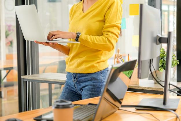 Programista stoi, przenosi i używa laptopa do testowania systemu w biurze.
