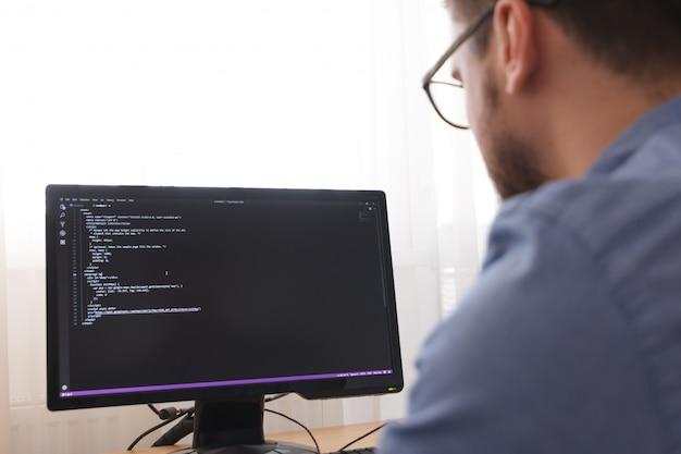 Programista w glsses, wpisując nowe linie kodu html. projektowanie stron internetowych i koncepcja rozwoju sieci. praca niezależna, los angeles, kalifornia - 25.10.2019