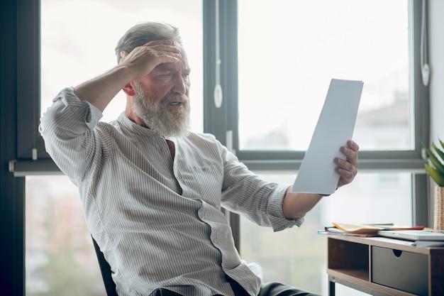 Projekt. biznesmen w średnim wieku trzymający papiery i oceniający je
