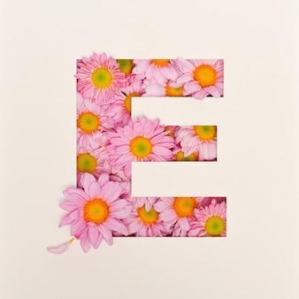Projekt czcionki, abstrakcyjna czcionka alfabetu z różowym kwiatkiem, realistyczna typografia kwiatowa - e.