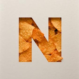Projekt czcionki, abstrakcyjna czcionka alfabetu z trójkątnymi chipsami kukurydzianymi, realistyczna typografia liści - n