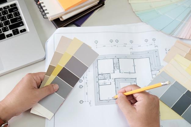 Projekt graficzny i próbki kolorów i długopisy na biurku. rysunek architektoniczny z narzędziami roboczymi i akcesoriami.