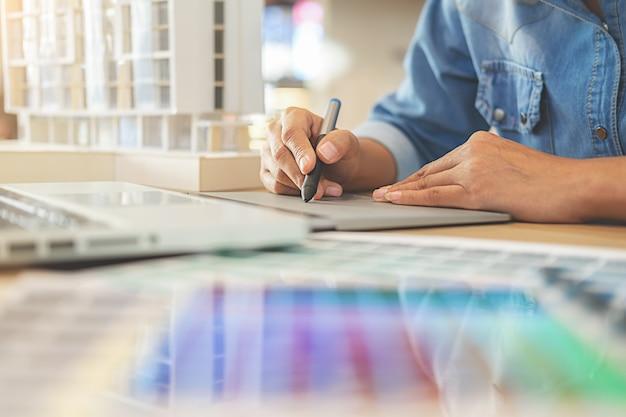 Projekt graficzny i próbki kolorów i pióra na biurku.