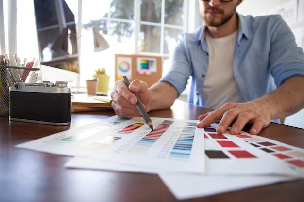 Projekt graficzny, próbki kolorów i długopisy na biurku
