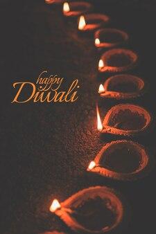 Projekt kartki z życzeniami happy diwali przy użyciu lamp olejnych beautiful lit diya or clay