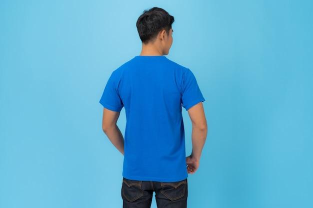 Projekt koszulki, młody człowiek w niebieskiej koszulce na białym tle na niebieskim tle