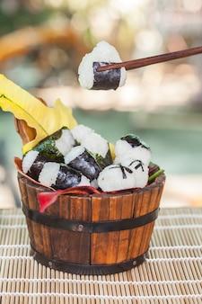 Projekt kulki ryżu piłkę w drewniane wiaderko