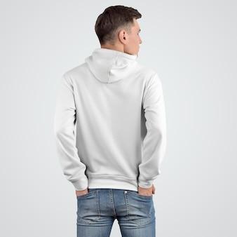 Projekt makiety z białą bluzą z kapturem na młodym mężczyźnie stojącym plecami. prezentacja szablonu modnych ubrań do sklepu. nowoczesna odzież