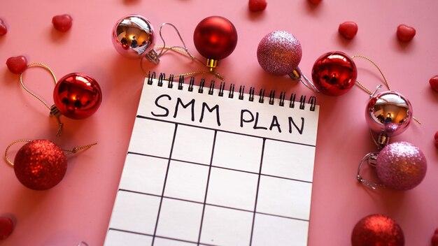 Projekt niezależny. plan smm jest pusty. białe prześcieradło na różowym świątecznym tle z czerwonymi bombkami i cukierkami w formie serc