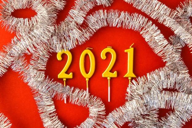 Projekt nowego roku 2021. data określona przez świece w pobliżu jodły na czerwonym tle widok z góry miejsca kopiowania. wesołych świąt, czerwone ozdoby świąteczne. bombki choinkowe