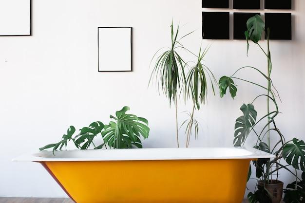 Projekt poddasza wnętrze łazienki lub pokoju. białe ściany z bezpłatnym copyspace. trend zielony - liście palmowe na tle. nowoczesna żółta wanna.