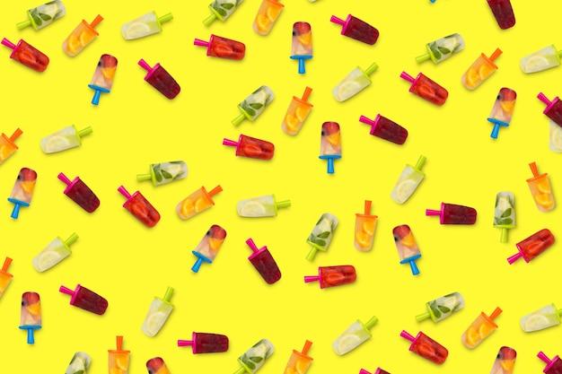 Projekt popsicles owocowych na żółtej powierzchni.