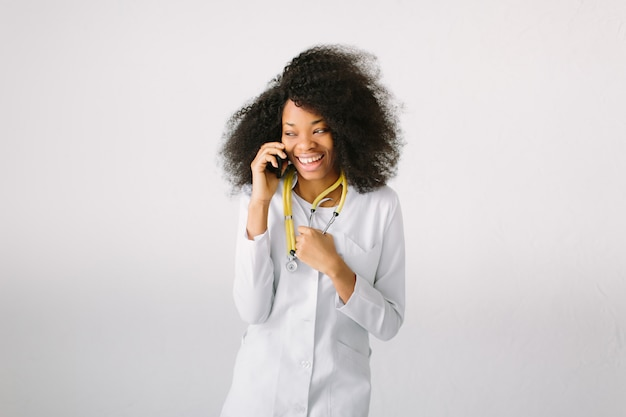 Projekt reklamy medycznej. młoda piękna dziewczyna afroamerykańskiej dziewczyny w białym płaszczu ze stetoskopem i folderu w szpitalu. bezosobowe szerokie tło. rozmawiać przez telefon