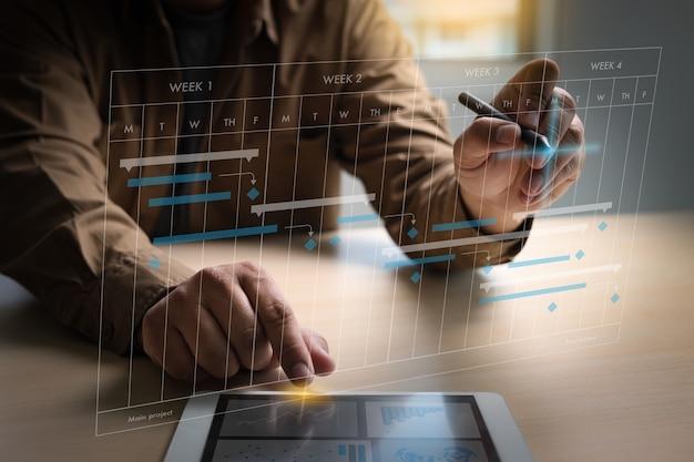 Projekt roboczy biznesmena i aktualizacja wirtualnego diagramu planowania i postępu wykresu oprogramowania gantta