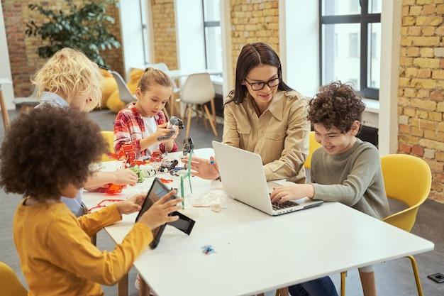 Projekt rodzaju młoda nauczycielka w okularach pokazująca naukowy film o robotyce małemu chłopcu za pomocą