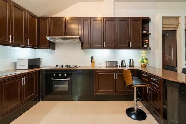 Projekt wnętrz domu, domu, willi i mieszkania obejmuje drewniany wbudowany blat kuchenny, stołek, okap, piekarnik, kuchenkę mikrofalową i szafkę