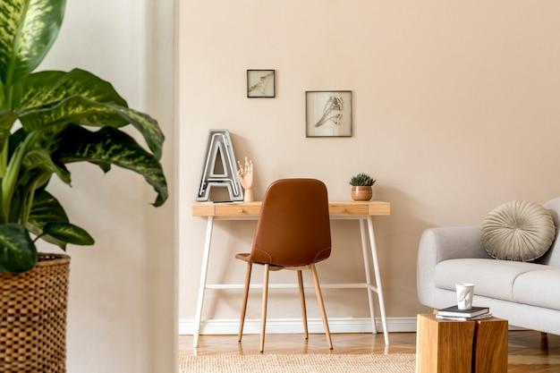 Projekt wnętrz skandynawskiej otwartej przestrzeni z makietą ramek na zdjęcia, drewnianym biurkiem, szarą sofą, roślinami, biurem z książkami i akcesoriami osobistymi. stylowa neutralna home staging. beżowe ściany. szablon.
