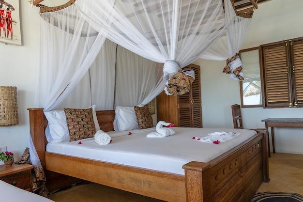 Projekt wnętrz, wyposażenie luksusowego domu wakacyjnego w willi z łóżkiem z baldachimem. projekt wnętrz tropikalnej willi nad morzem na wyspie zanzibar, tanzania, afryka wschodnia