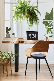 Projekt wnętrza domowego biura ze stylowym drewnianym biurkiem, pięknym krzesłem, laptopem, tabletami, książką i eleganckimi akcesoriami osobistymi w przytulnym wystroju domu.
