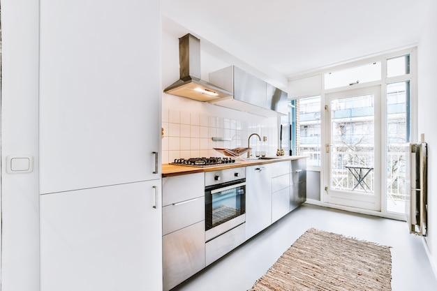 Projekt wnętrza domowej kuchni z oknem oraz nowoczesnymi lekkimi meblami i wyposażeniem z wykładziną na podłodze