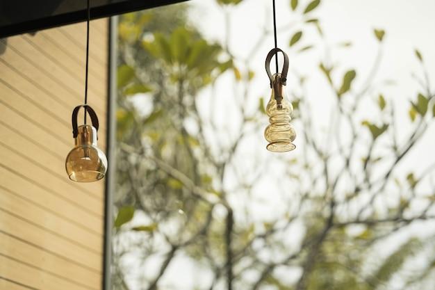 Projekt wnętrza lampy. żarówka led świeci i wisi pod dachem domu.