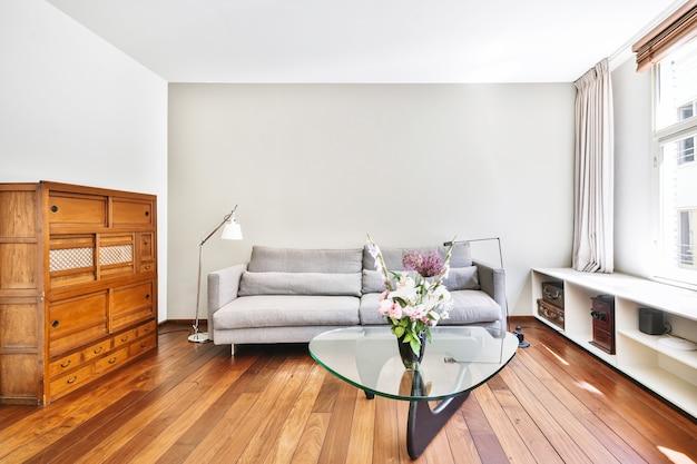 Projekt wnętrza nowoczesnego przestronnego, jasnego, otwartego apartamentu z dużymi oknami wyposażonymi w funkcjonalną rozkładaną sofę i szklany stolik