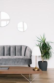 Projekt wnętrza nowoczesnego salonu z szarą sofą, stolikiem kawowym i palmą na doniczce.