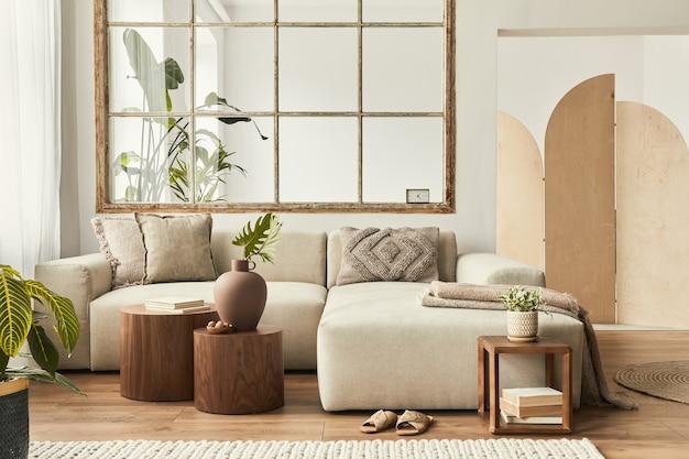 Projekt wnętrza salonu ze stylową beżową sofą modułową, drewnianymi stolikami kawowymi, roślinami, poduszkami, kratą, neutralnym parawanem, dekoracją i eleganckimi dodatkami.