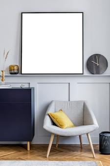Projekt wnętrza salonu ze stylową granatową komodą szary fotel poduszka czarny zegar suszony kwiat nowoczesna dekoracja obrazów i eleganckie dodatki w wystroju domu