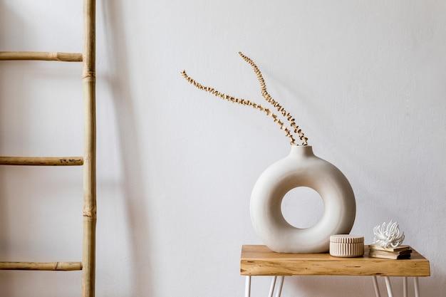 Projekt wnętrza salonu ze stylowymi suszonymi kwiatami w wazonie, drewnianą drabiną, pledem i osobistymi dodatkami w nowoczesnym wystroju domu.