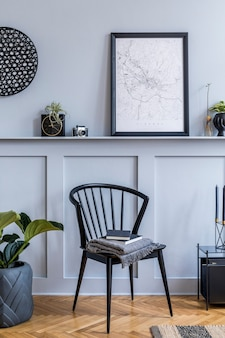 Projekt wnętrza skandynawskiego salonu z czarną mapą plakatową, stylowym krzesłem, czarnym stolikiem kawowym, roślinami, dekoracją, dywanem, książką i eleganckimi dodatkami osobistymi.