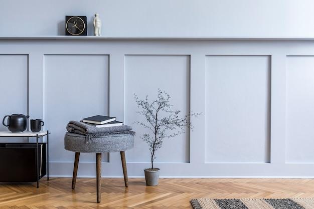 Projekt wnętrza skandynawskiego salonu z nowoczesnym stolikiem kawowym, szarym taboretem, pledem, rośliną, czarnym zegarem, czajnikiem i eleganckimi akcesoriami osobistymi w stylowym wystroju domu. skopiuj miejsce.