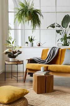 Projekt wnętrza skandynawskiej otwartej przestrzeni z żółtą aksamitną sofą, roślinami, meblami, książką, drewnianą kostką i osobistymi akcesoriami w stylowej home staging.
