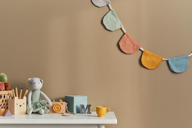Projekt wnętrza stylowej przestrzeni dziecięcego pokoju z białą półką, drewnianymi zabawkami, akcesoriami dla dzieci, przytulną dekoracją i wiszącymi bawełnianymi flagami na beżowej ścianie