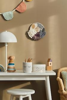 Projekt wnętrza stylowej przestrzeni pokoju dziecięcego z białym biurkiem, drewnianymi zabawkami, akcesoriami dla dzieci, białą lampą, przytulną dekoracją i wiszącymi bawełnianymi flagami na beżowej ścianie