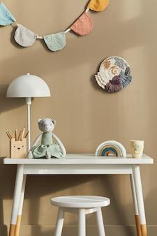 Projekt wnętrza stylowej przestrzeni pokoju dziecięcego z białym biurkiem, drewnianymi zabawkami, akcesoriami dziecięcymi, białą lampą, przytulną dekoracją i wiszącymi bawełnianymi flagami na beżowej ścianie.