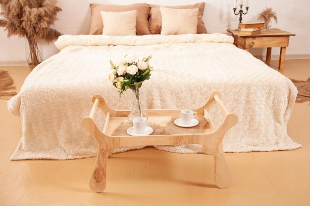 Projekt wnętrza sypialni z pampasami, roślinami, świecami.