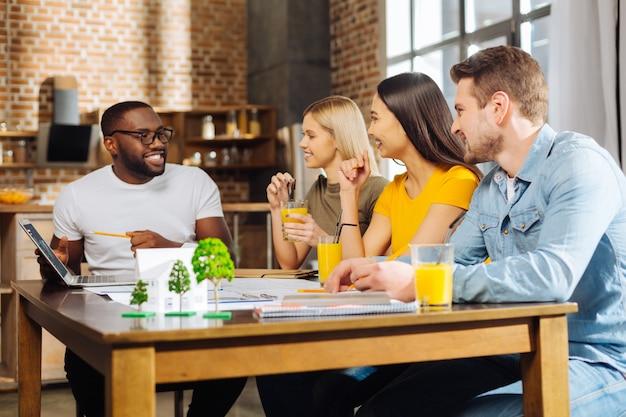 Projekt zespołowy. czterech atrakcyjnych, wesołych młodych uczniów pracujących przy stole, zastanawiając się i omawiając strategię