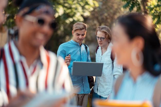 Projekt zespołowy. dwóch skoncentrowanych studentów stojących za kolegami z grupy i pracujących nad swoim projektem na laptopie poza uniwersytetem.