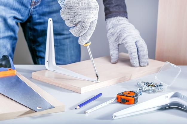 """Projekt """"zrób to sam"""". człowiek naprawia lub montuje meble. koncepcja montażu mebli."""