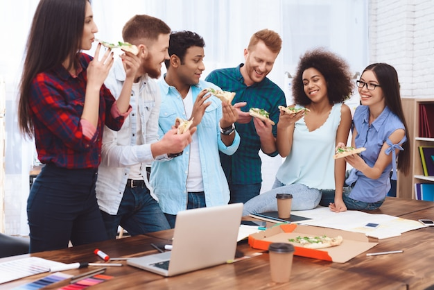 Projektanci gurppa jedzą pizzę.