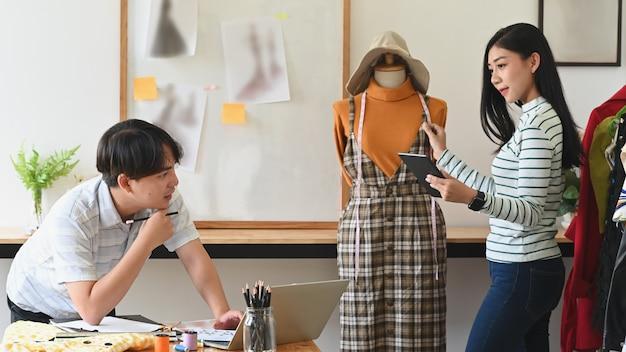 Projektanci mody pracujący nad pomiarem manekina