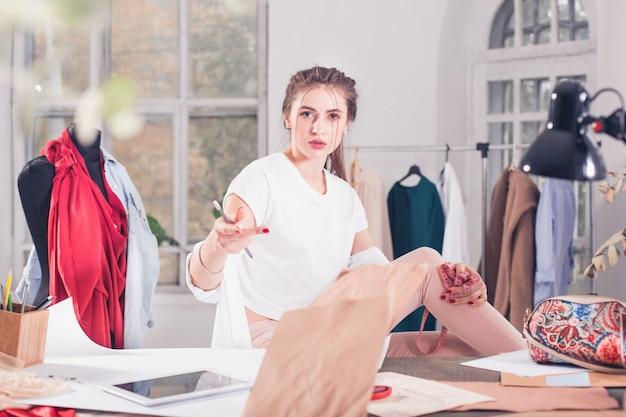 Projektanci mody pracujący w studio siedzi na biurku