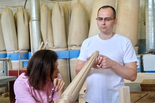 Projektanci płci męskiej i żeńskiej, stolarze, inżynierowie pracujący w warsztacie przemysłowym.