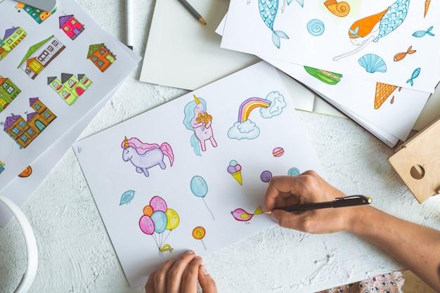 Projektant animatorów rysuje kolorowe szkice różnych postaci.
