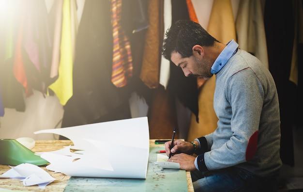 Projektant butów pracujący z modelami papierowymi do cięcia skóry.