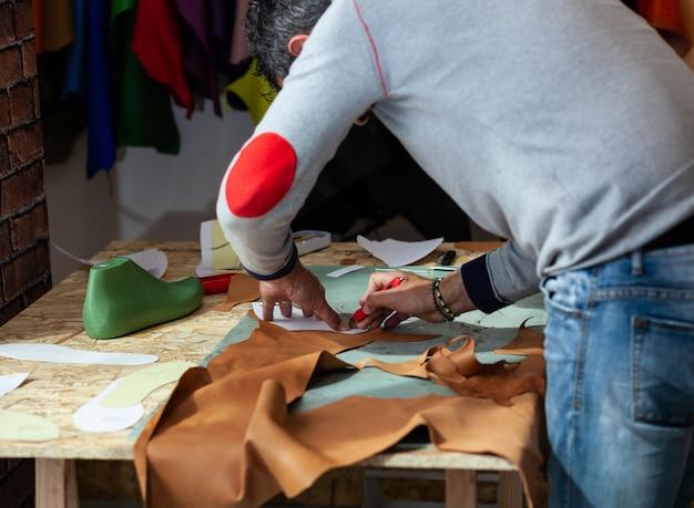 Projektant butów pracujący ze skórą.