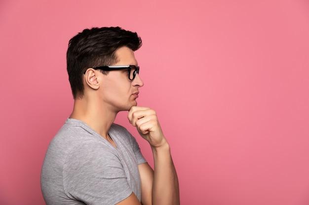 Projektant. bystry mężczyzna w szarym t-shircie i okularach, który stoi z profilu i myśli o czymś, dotykając lewą ręką brody.