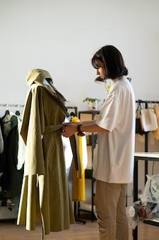 Projektant dopasowuje płaszcz na manekinie w studio pracownica atelier pracy przy kolekcji w warsztacie
